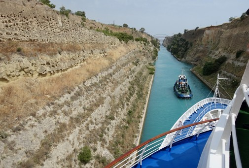 The tug guides the ship through the narrow 'cut' in the land of the Corinth Canal