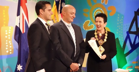 The Lord Mayor of Sydney, the Honourable Clover Moore presents Rabeh with his Australian Citizenship Certificate with Alex Greenwich MP looking on.