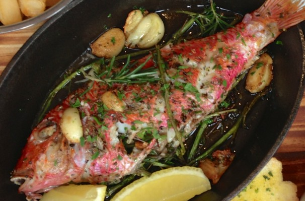 Red Mullet, sauteed and then roasted on rosemary branches and sweet cloves of roasted garlic .
